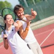 Two happy tennis players with thumbs up — Stock Photo