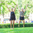 Two Blonde Girls Jumping at Park — Stock Photo