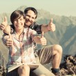 Foto Stock: Young Couple with Thumbs Up at Top of Mountain