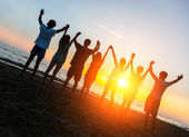 Group of People with Raised Arms looking at Sunset — Stockfoto