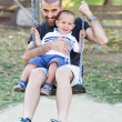 Stock Photo: Little Boy Playing on Swing with Father or Uncle