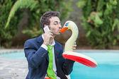 śmieszne młody biznesmen z swimmingtrunks przy basenie — Zdjęcie stockowe
