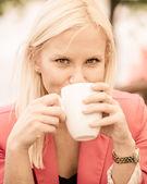 Joven mujer sosteniendo la taza de café — Foto de Stock