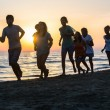 Stock Photo: Group of People Running on the Beach at Sunset