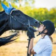 Young Woman Kissing a Black Stallion Horse — Stock Photo