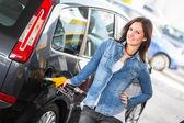 Mladá žena, plní její auto u čerpací stanice — Stock fotografie
