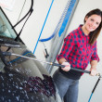 ung kvinna tvätta bil — Stockfoto