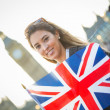 Young Woman Holding Union Jack in front of Big Ben — Stock Photo #34238363