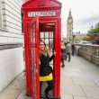 Young Woman next to London Traditional Telephone Booth — Stock Photo