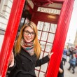 Young Woman next to London Traditional Telephone Booth — Stock Photo #34238653