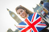 Young Woman Holding Union Jack in front of Big Ben — Stock Photo