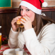 Stock Photo: Young WomEating Hamburger on Christmas Day