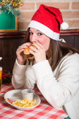Young Woman Eating Hamburger on Christmas Day — Stock Photo