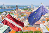 Latvian and Europena Flags with Riga Cityscape on Background — Stock Photo