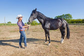 Cowgirl with a Black Stallion Horse — Stock Photo