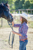 Cowgirl s koněm černý hřebec — Stock fotografie