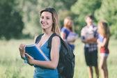 молодая студентка в парке с другими друзьями — Стоковое фото