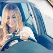 Stock Photo: Young WomSending Messages while Driving