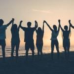 Skupina lidí se vztaženými pažemi při pohledu na západ slunce — Stock fotografie #40081293