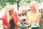 Two Women Using Digital Tablet at Bar — Stock Photo
