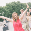 Girl with Raised Arms and Friends on Background — Stock Photo #43333987