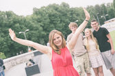Girl with Raised Arms and Friends on Background — Stock Photo