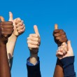 Multiracial Thumbs Up Against Blue Sky — Stock Photo #4492109