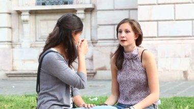 Zwei junge frauen auf einer bank im park — Stockvideo