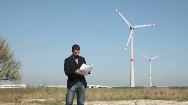 Engineer in front of Wind Turbine for Power Generation — ストックビデオ