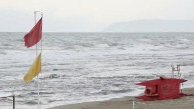 Drapeaux devant la mer démontée — Vidéo