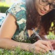 Woman writing in her diary on the lawn — Stock Video