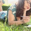 Woman writing in her diary on the lawn — Stock Video #49047973