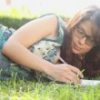 Woman writing in her diary on the lawn — Stock Video #49048075