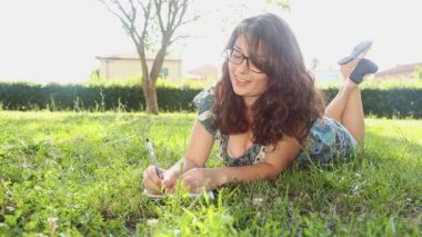 Woman writing in her diary on the lawn — Stockvideo