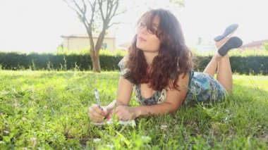 Woman writing in her diary on the lawn — Стоковое видео