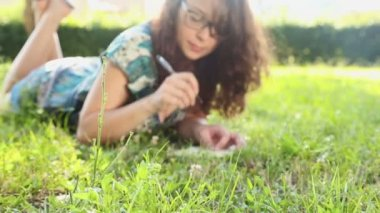 Woman writing in her diary on the lawn — Video Stock