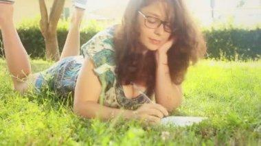 在她的日记写在草坪上的女人 — 图库视频影像