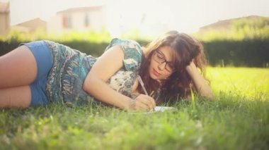 Woman writing in her diary on the lawn — 图库视频影像