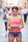 Beautiful Girl with Headphones and Digital Tablet in a Crowded S — Stock Photo