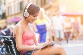 Schönes mädchen mit kopfhörern und digitale tablett in der stadt — Stockfoto