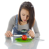 Girl investigating tomato. — Stock Photo