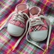 Foto de Stock  : Pair of sneakers on colorful fabric