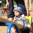 Child sitting on seesaw — Stock Photo
