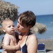 Mother with baby on beach - Stock Photo