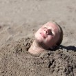 Girl buried in sand — Stock Photo