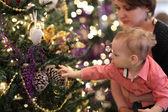 Baby touching Christmas tree — Stock Photo