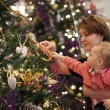 Mother with baby near Christmas tree — Stockfoto
