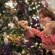 Mother with baby near Christmas tree — Stock Photo