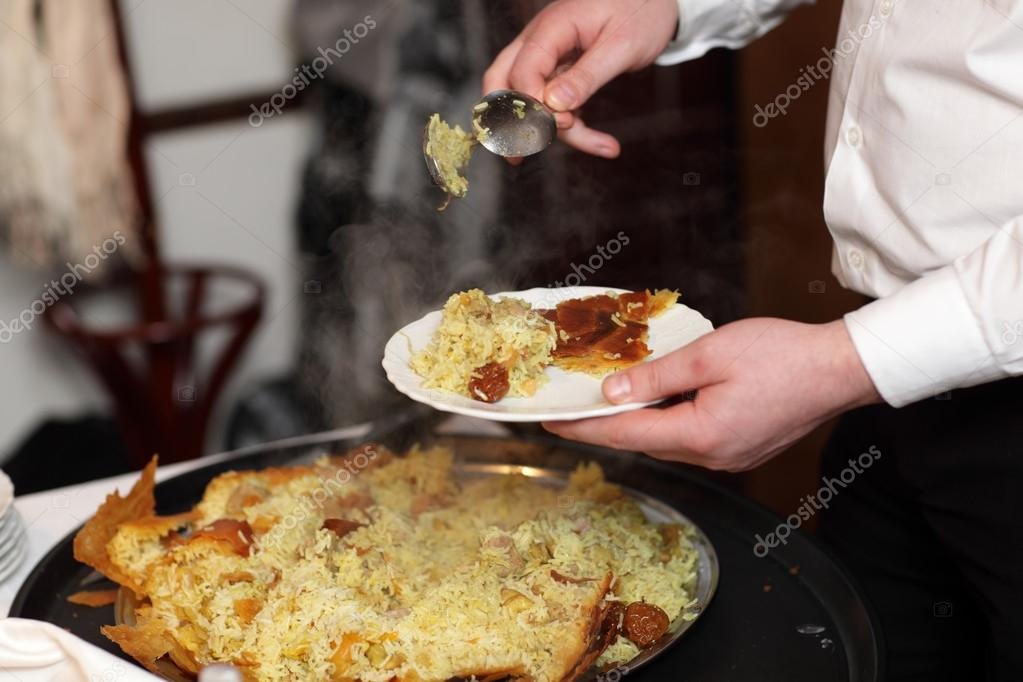 Chef is putting pilaf on a plate at an azerbaijani restaurant — Stock Photo #17991249