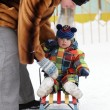 Mother puts toddler on sled — Stockfoto